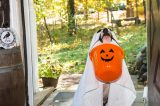 A dog dressed as a ghost holding a Halloween trick or treat pumpkin basket.