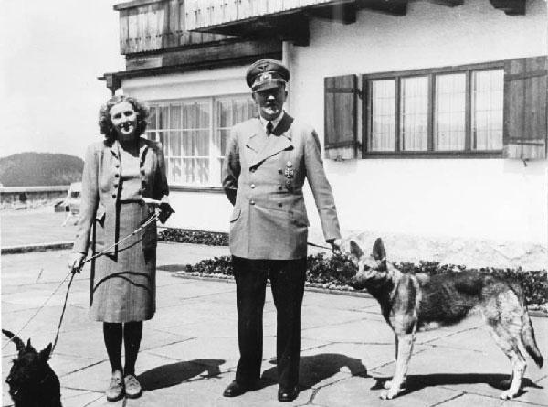 """Eva Braun and Hitler with their own dogs. """"Bundesarchiv B 145 Bild-F051673-0059, Adolf Hitler und Eva Braun auf dem Berghof"""" by Bundesarchiv, B 145 Bild-F051673-0059 / CC-BY-SA. Licensed under CC BY-SA 3.0 de via Wikimedia Commons."""