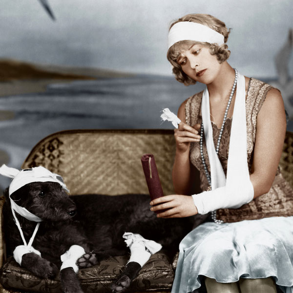 A flapper woman with a sick black dog.