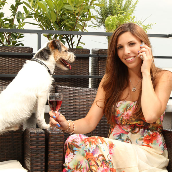A woman drinking wine with her dog.
