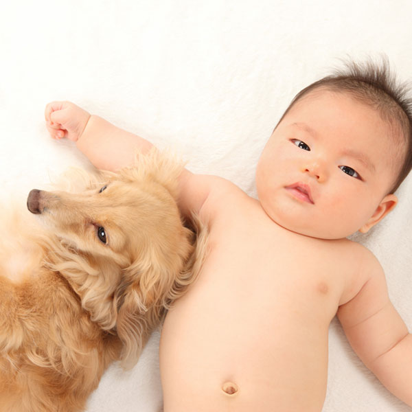 A baby human with a dog.