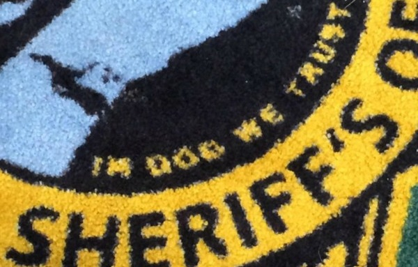 'In Dog We Trust' Works for Us on a Rug, But Not for a Florida Sheriff