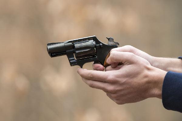Hands holding a pistol by Shutterstock.