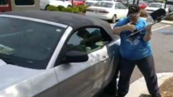Michael Hammons smashing the window of the car. (Screenshot: WAGA)