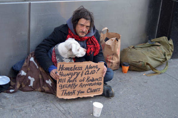 A homeless man with a dog and a sign.
