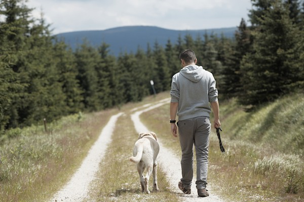 Man hiking with dog by Shutterstock.