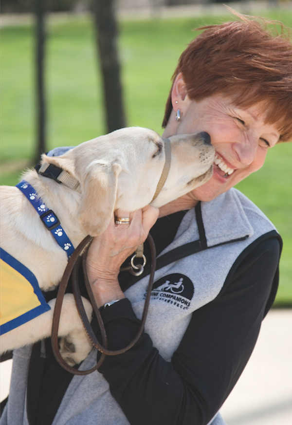 A puppy raiser with CCI gets canine kisses. (Photo courtesy Canine Companions for Independence)
