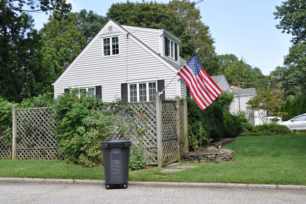 Trash can in front of house by Shutterstock.