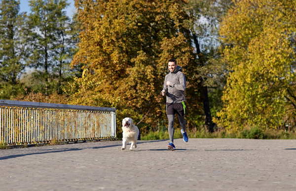 Man running with dog by Shutterstock.