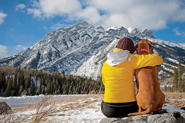 Woman and dog with mountain view by Shutterstock.