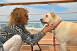 A woman with a yellow dog on a cruise ship.