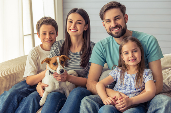 A family on a couch with their small dog.