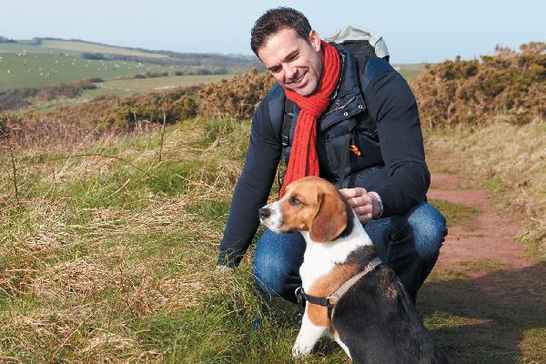 A man hiking with a Beagle dog.