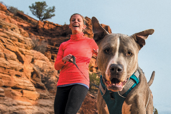 Woman hiking and running with her dog.