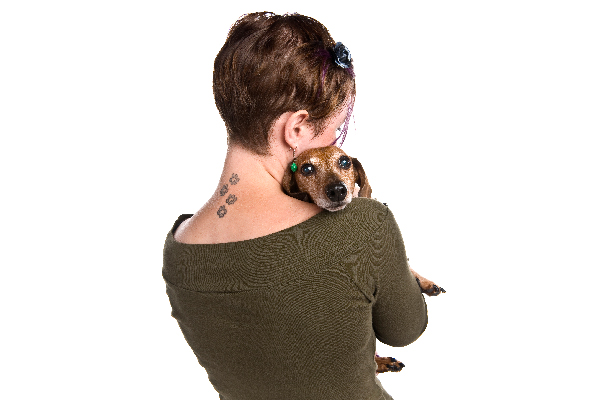 A woman with tattoos on the back of her neck hugging a dog.