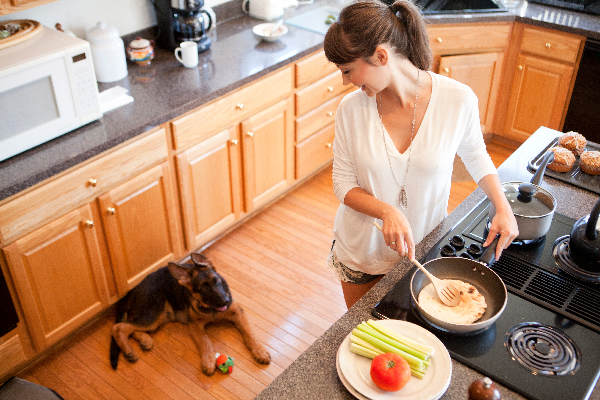 A woman cooking with tomatoes while her dog looks on.