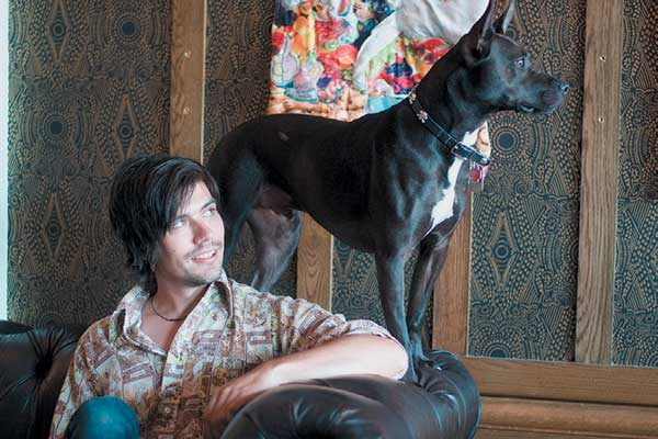 There's no surprise that dogs and art abound at the Old No. 77 in New Orleans. Pictured with a canine friend is the 2016 artist in residence TJ Kiser.