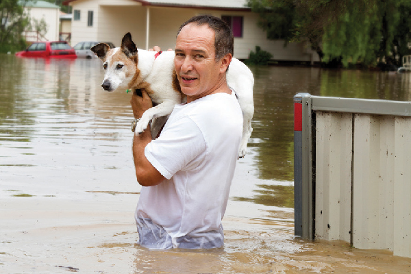 Man wading in flood, carrying dog.