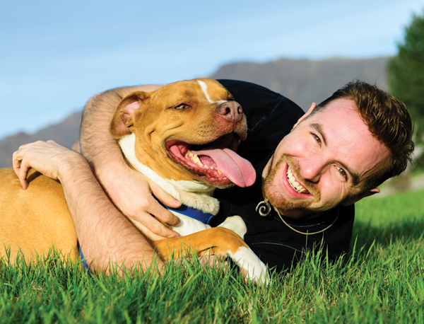 Dog and owner rolling around in grass.